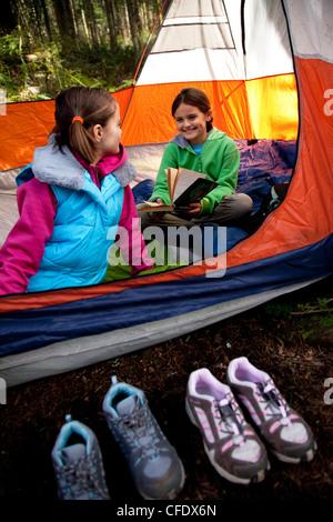 Zwei junge Mädchen in einem Zelt zu lesen. - Stockfoto