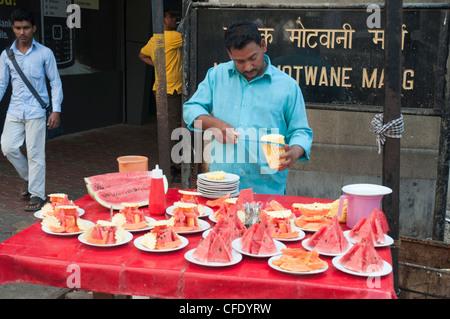 Mann bereitet Teller mit frischem Obst Snacks zum Verkauf in der Innenstadt von Fort Bezirk von Mumbai (Bombay), - Stockfoto