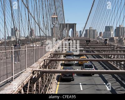 Fußgänger sind auf einer separaten Ebene vom Autoverkehr auf der Brooklyn Bridge in New York City. - Stockfoto