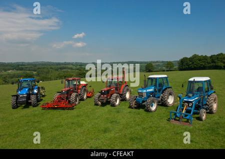 Eine Reihe von landwirtschaftlichen Traktoren in einem grünen Feld in der Nähe von Battle Abbey. Sussex, England, - Stockfoto