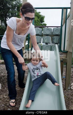 Mutter und hier Babymädchen spielt in der Rutschbahn. - Stockfoto