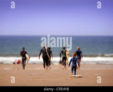 Ein kleiner Junge mit einem Bodyboard versucht aufzuholen mit seiner Familie an einem Frühlingstag im Rhossili Bay - Stockfoto