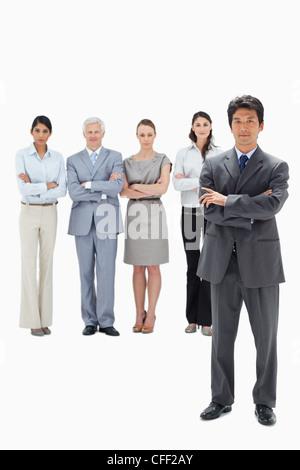Business-Team mit ihren verschränkten Armen und einem asiatischen Mann im Vordergrund - Stockfoto