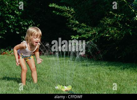 Junge Blonde Mädchen spielt in einem Rasensprenger, USA - Stockfoto
