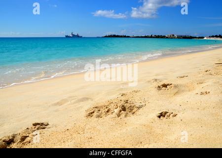 Landschaftsfoto Küstenlinie mit Fußspuren im Sand, türkisfarbenes Wasser und Horizont. - Stockfoto