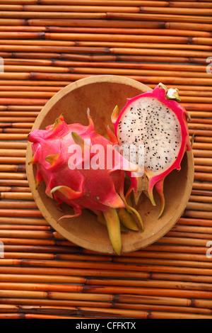 Ganze und halbe Drachenfrucht in Holzschale auf Bambus-Hintergrund