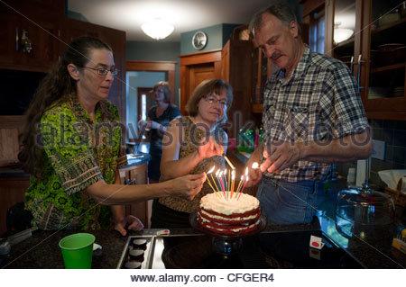 Familienmitglieder versammeln sich um einen Geburtstagskuchen, die Kerzen anzünden. - Stockfoto