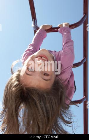 Junges Mädchen kopfüber am Klettergerüst, Toronto, Ontario - Stockfoto