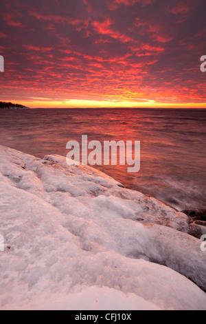 Eisigen Küste und bunten Himmel in der Abenddämmerung am Larkollen in Rygge, Østfold Fylke, Norwegen. - Stockfoto