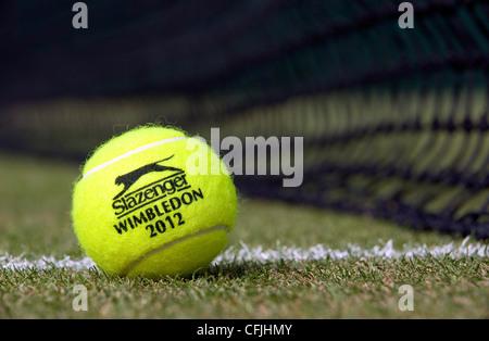 Slazenger Wimbledon 2012 Tennisball sitzt auf einem Rasenplatz durch das Netz - Stockfoto