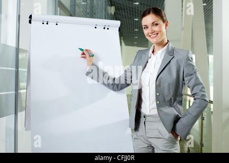 Lächelnde Geschäftsfrau präsentiert neues Projekt auf einem whiteboard - Stockfoto