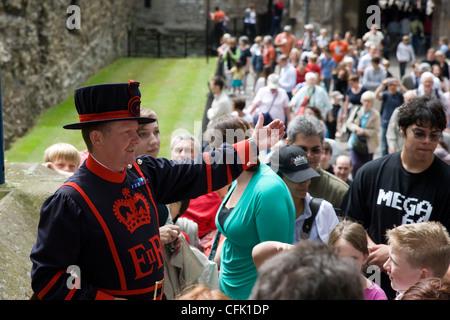 Yeoman Guard oder Beefeater geben einen geführte Tour-Kommentar zu einer Menge von Touristen an den Tower of London, - Stockfoto