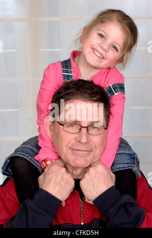 Großvater geben seine kleine Enkelin eine Huckepack Fahrt - Stockfoto