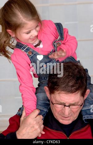 Enkelkind Hänseleien Großvater während er seine kleine Enkelin eine Huckepack Fahrt geben - Stockfoto