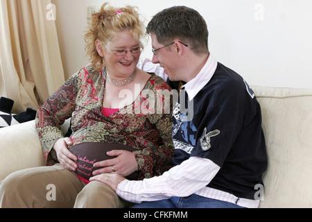 Erwachsenes paar schwangere sprechen, dritten Trimenon der Schwangerschaft, sie sind glücklich, zu Hause auf Sofa - Stockfoto