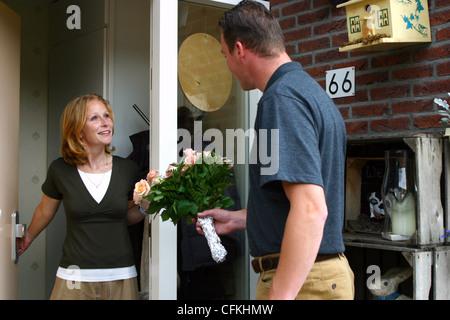 Mann an der Haustür bietet einen glückliche Frau Blumenstrauß - Stockfoto