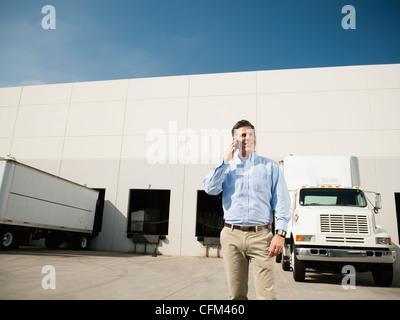 USA, Kalifornien, Santa Ana, Geschäftsmann Gespräch am Telefon außerhalb Lager - Stockfoto