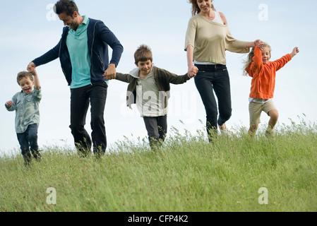 Familie laufen Hand in Hand im Bereich - Stockfoto