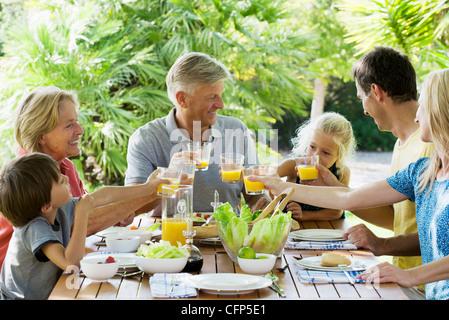 Mehr-Generationen-Familie Toasten mit Orangensaft im Freien, Porträt - Stockfoto