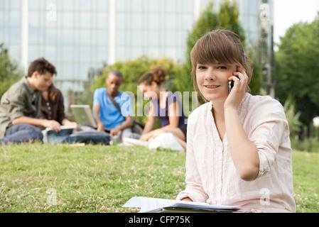 Junge Frau am Handy, Leute im Hintergrund, Porträt - Stockfoto