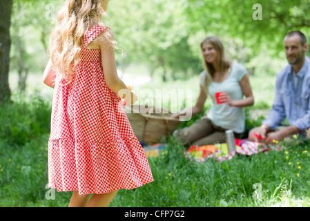 Mädchen mit Picknick mit den Eltern im Freien, Rückansicht - Stockfoto