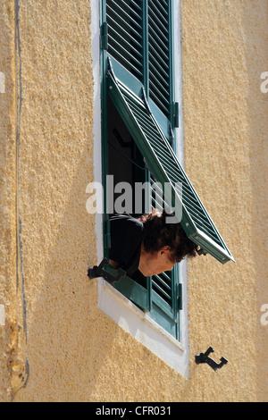 alte Dame schaut aus dem Fenster - Stockfoto