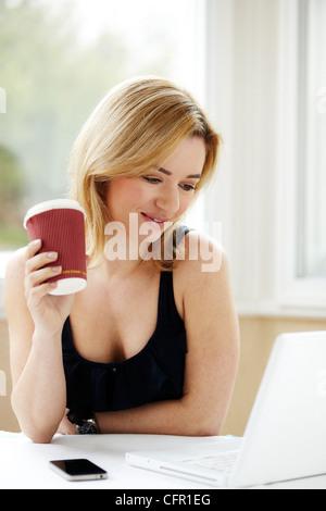Frau mit Laptop in der Küche - Stockfoto