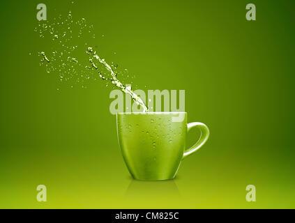 Grüne Becher mit Wasser spritzt. - Stockfoto