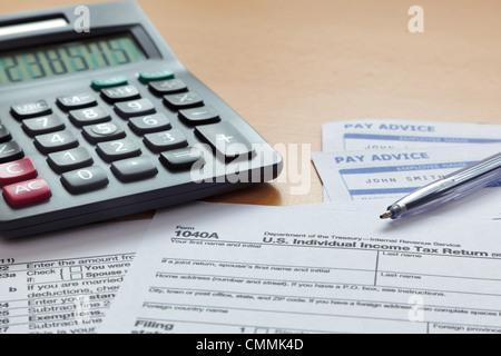 Foto von einer leeren 1040 Steuerformular mit Gehaltsabrechnungen und Rechner. - Stockfoto