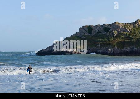 Eine Surfer geht am Broadhaven Beach, West Wales ins Meer. - Stockfoto