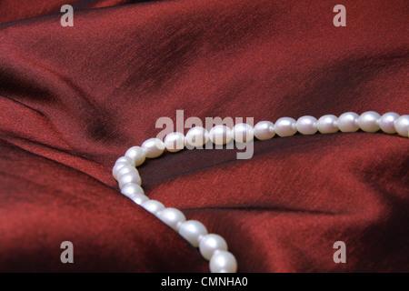 Weiße Perlenkette auf dunkelrot satin. - Stockfoto