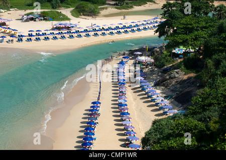 Sonnenschirme am Sandstrand mit kristallklarem türkisfarbenem Wasser entlang Naiharn Beach, Insel Phuket, Thailand - Stockfoto