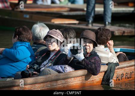 Japanische Touristen mit Kameras in einem Punt in Cambridge UK - Stockfoto