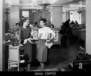 1940ER JAHREN ZWEI FRAUEN BÜROANGESTELLTEN DURCH BÜRO STEHEN WASSER KÜHLER SPRECHEN - Stockfoto