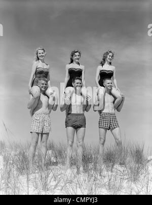 1950S 1960S AUF DÜNEN MIT FRAUEN IN IDENTISCHEN BADEANZÜGE AUF MÄNNER SCHULTERN SITZEN DREI PAARE AM STRAND - Stockfoto