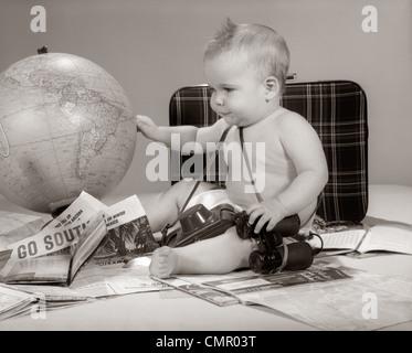 1960ER JAHRE BABY SITZEND BETRACHTEN GLOBUS MIT KAMERA-FERNGLAS KOFFER & REISEBROSCHÜREN - Stockfoto