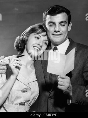 1960ER JAHREN PAAR BUCHSTABEN GLÜCKLICHE FRAU RUHT LESEKOPF AUF MANS SCHULTER - Stockfoto