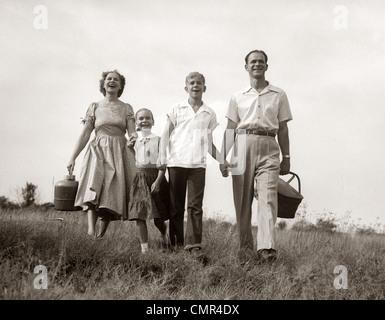 1950ER JAHRE FAMILIE WANDERN IN WIESE MIT SOMMER-PICKNICK-KORB UND THERMOSKANNE - Stockfoto