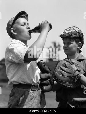 1930ER JAHREN PAAR JUNGS BASEBALL HANDSCHUHE MIT CATCHERS MASKE BEOBACHTEN ANDERE TRAGEN CAP GETRÄNKEFLASCHE SODA - Stockfoto
