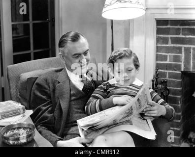 1930S 1940S GROßVATER MIT ENKEL AUF RUNDE LESEN SONNTAG ZEITUNG COMICS ZUSAMMEN IM WOHNZIMMER SITZT - Stockfoto