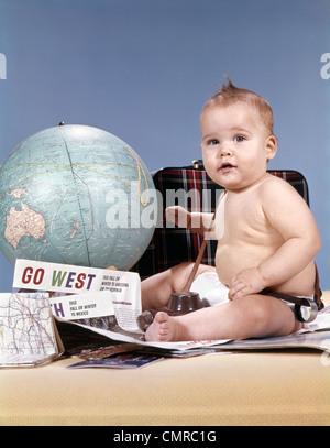 1960ER JAHRE BABY BOY WELTKUGEL MIT KOFFER UND REISE-UTENSILIEN, BLICK IN DIE KAMERA ZU SITZEN - Stockfoto