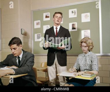1960ER JAHRE TEEN STUDENTEN BOYS GIRLS KLASSENZIMMER JUNGE STEHEND LESUNG AUS NOTEBOOK HIGH SCHOOL RETRO - Stockfoto