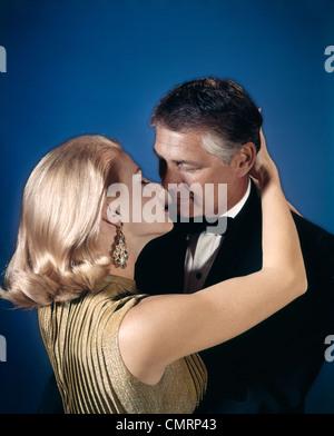 ROMANTISCHES PAAR MANN FRAU ABENDKLEID STUDIO 1970ER JAHREN KÜSSEN UMARMEN - Stockfoto