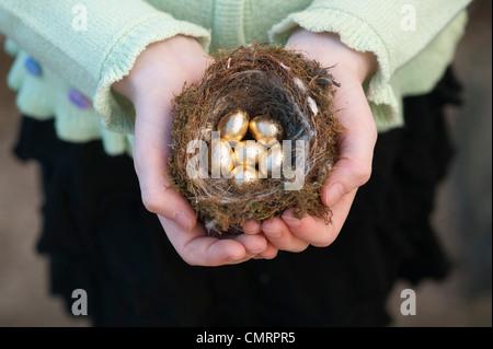 Mädchen mit goldenen Eiern in einem Vogelnest - Stockfoto