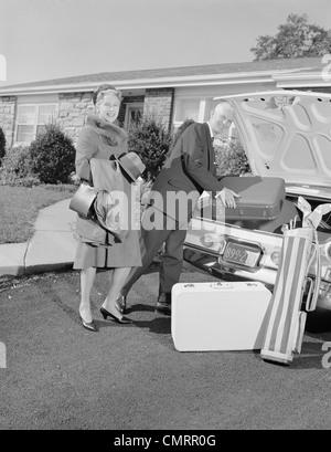 1960ER JAHRE ÄLTEREN MANN FRAU MANN FRAU VERPACKUNG STAMM MIT GEPÄCK - Stockfoto