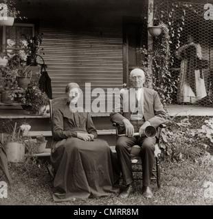 1890S 1900S PORTRAIT ÄLTERES PAAR SITZEN IM GARTEN MANN MIT OHR-TROMPETE - Stockfoto