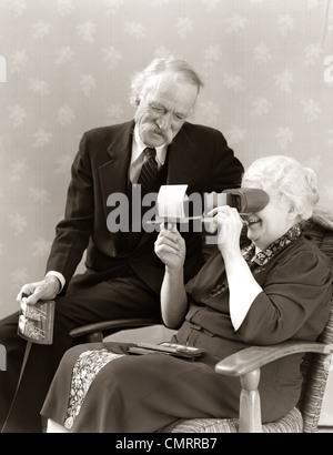 1940ER JAHRE ÄLTEREN ÄLTERES PAAR MANN FRAU BETRACHTEN VON FOTOS VON DIAPROJEKTOR STEREOSKOP - Stockfoto