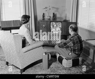 1950ER JAHREN PAAR MANN FRAU KONSOLE FERNSEHEN IM WOHNZIMMER - Stockfoto