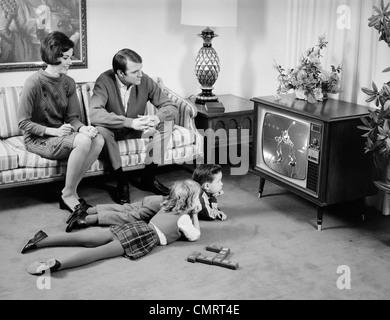 1960ER JAHRE FAMILIE VOR DEM FERNSEHER IM WOHNZIMMER ELTERN AUF COUCH KINDER AM BODEN LIEGEND 4 - Stockfoto