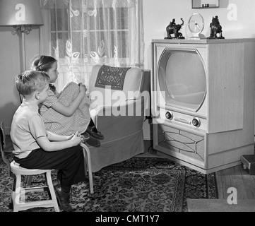 1950ER JAHREN JUNGEN UND MÄDCHEN BEOBACHTEN FERNSEHER IM WOHNZIMMER - Stockfoto
